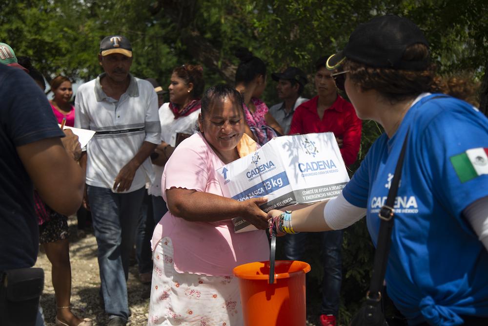 Una mujer recibe despensas en Tabasco.